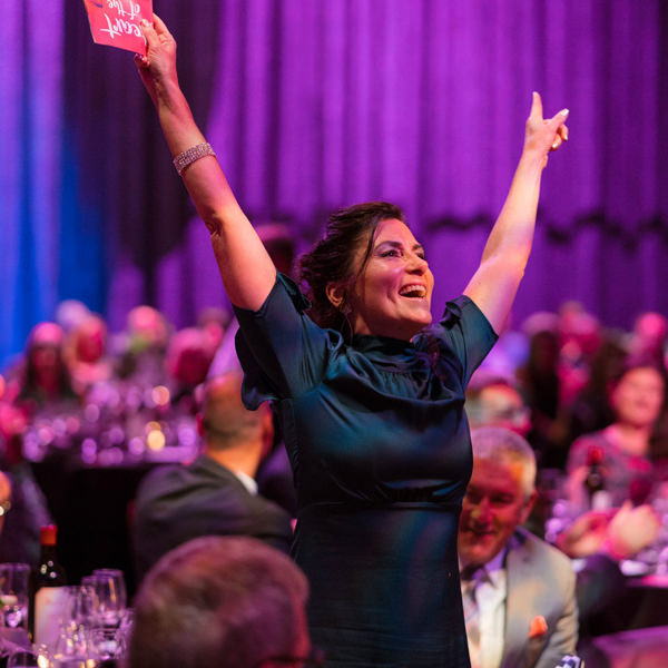 Woman with her arms raised in excitement at the Heart of the Arts Gala