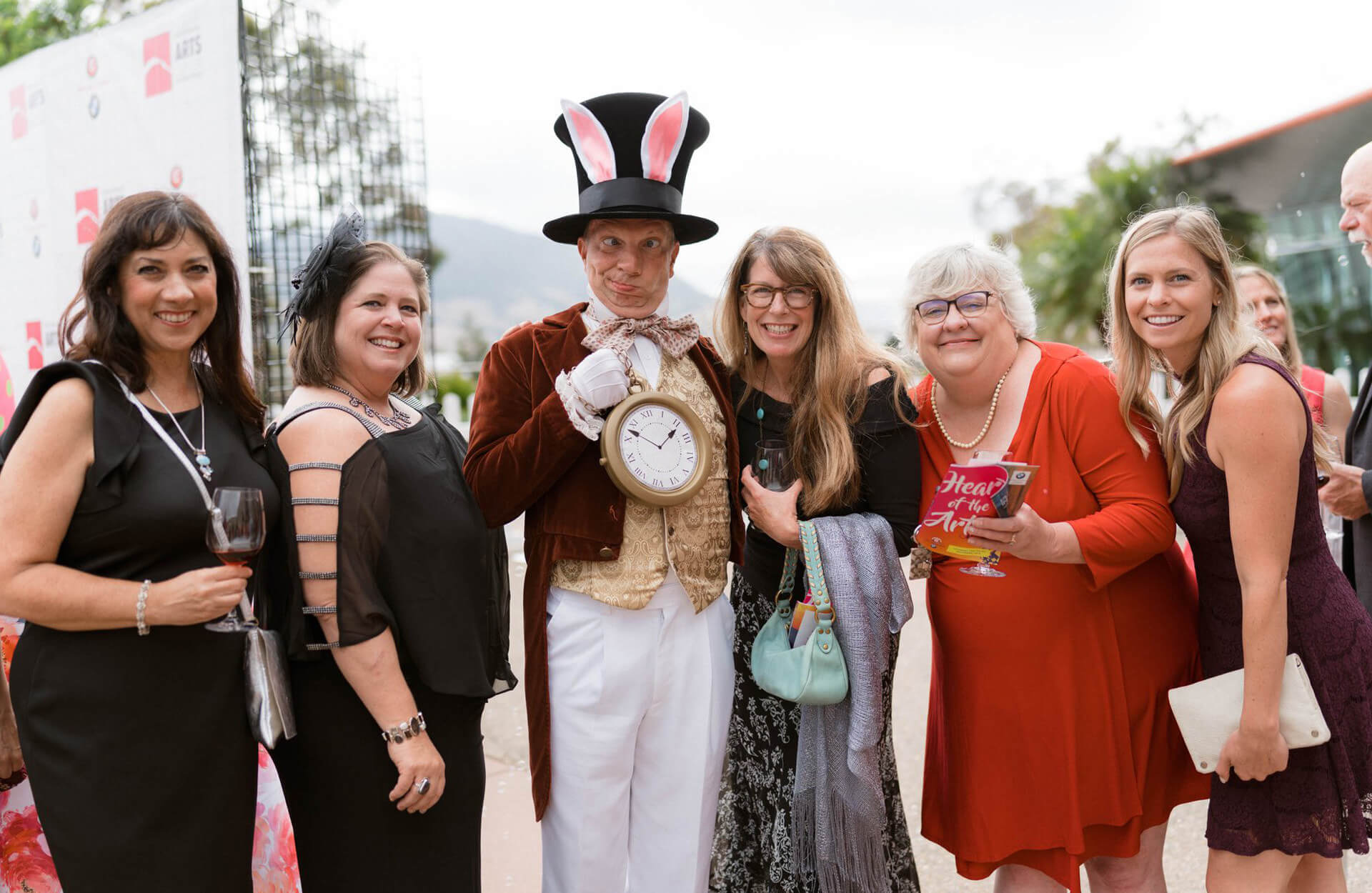 Group of people posing with the Mad Hatter at the Heart of the Arts Gala