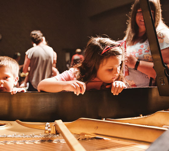 Children looking inside of a piano